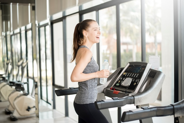 Pretty young sport woman is drinking water on treadmill in gym, healthy lifestyle