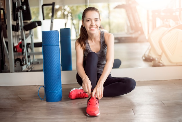 Pretty young sport woman is tying her sneakers in gym, healthy lifestyle