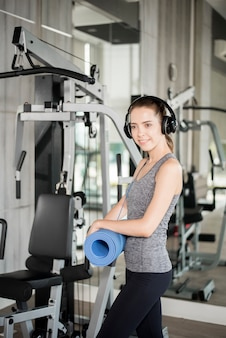 Pretty young sport woman is workout with mat  in gym, healthy lifestyle