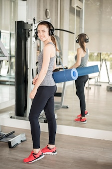 Pretty young sport woman is workout with mat  in gym