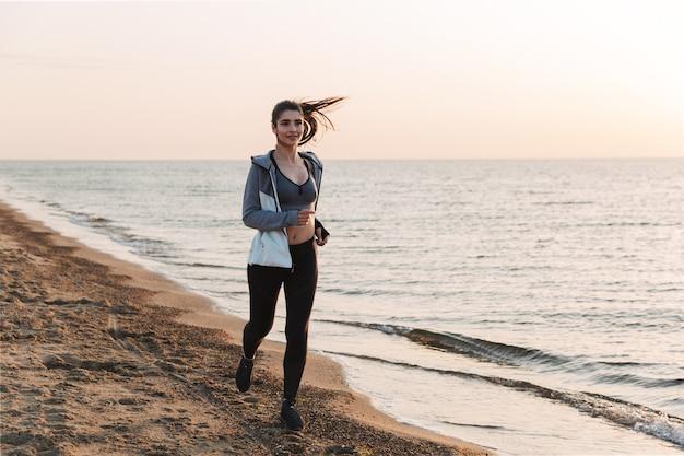 해변에서 실행 꽤 젊은 sportswoman