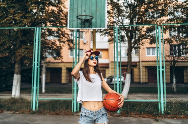 Pretty young sporty girl with basketball ball outdoor.