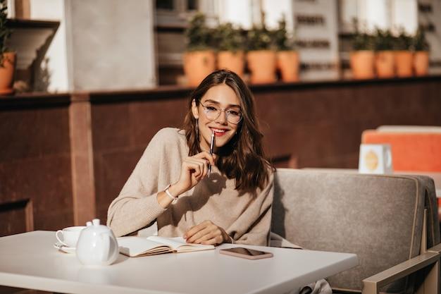 Ragazza abbastanza giovane studentessa con acconciatura ondulata scura, trucco alla moda, occhiali e pullover beige, studiando alla terrazza del caffè della città in una calda giornata autunnale