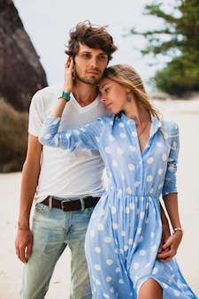 Pretty young stylish hipster couple in love on tropical beach during vacation