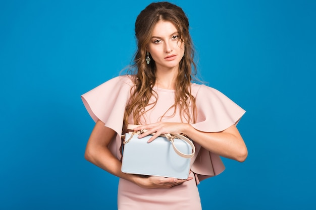 Pretty young stylish sexy woman in pink luxury dress, summer fashion trend, chic style, blue studio background, holding trendy handbag