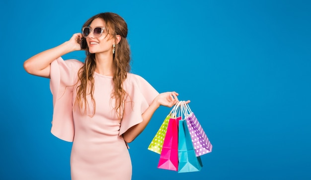 Pretty young stylish sexy woman in pink luxury dress, summer fashion trend, chic style, sunglasses, blue studio background, shopping, holding paper bags, talking on mobile phone, shopaholic