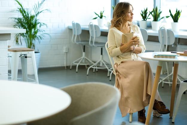 彼女の友人を待っている間、コーヒーブレイクで居心地の良いカフェのテーブルのそばに座って本と飲み物を持つかなり若いスタイリッシュな学生
