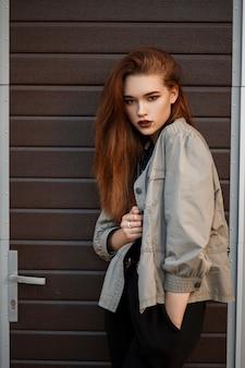 패션 봄 재킷과 검은 색 폴로 셔츠에 꽤 젊은 세련된 여자는 거리의 게이트 근처에 서