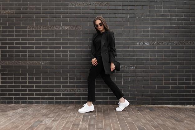 ビジネスブレザーとハンドバッグと白いスニーカーでファッショナブルな黒いウールの服を着たかなり若いスタイリッシュな女性は、通りの黒いレンガの壁の近くを歩きます