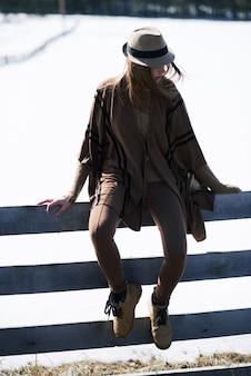 모자에 꽤 젊은 세련된 여자, 겨울에 농촌 환경에서 눈 더미의 배경에 나무 울타리에 앉아 leggins amd 격자 무늬