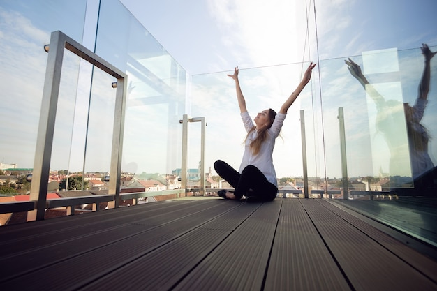 Pretty young stylish woman or model in the open air place or observation deck enjoys new day