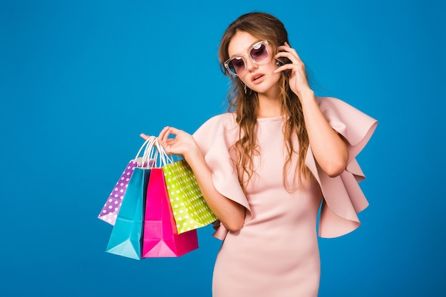 Pretty young stylish woman in pink luxury dress using a mobile phone and holding shopping bags