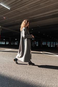 긴 코트에 곱슬머리를 한 꽤 젊고 세련된 여성이 주차장에서 길을 걷고 있습니다. 도시 여성 스타일