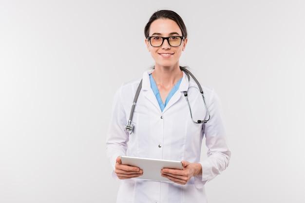 カメラの前で単独でネットワーキングしながらデジタルタブレットを保持しているホワイトコートのかなり若い成功した臨床医