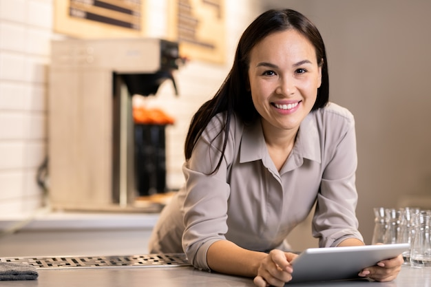 Pretty young successful entrepreneur with touchpad looking at you with smile while working in her restaurant