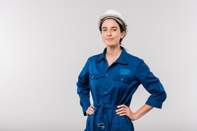 Довольно молодая успешная женщина-инженер в синей спецодежде и защитном шлеме держит руки изолированно на талии