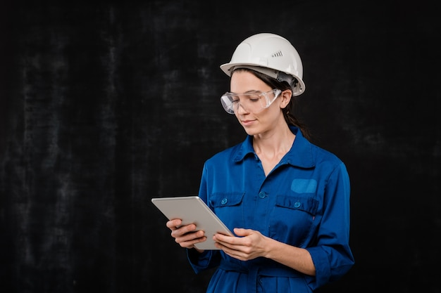 Pretty young technician in hardhat and blue workwear looking at touchpad screen while surfing in the net in isolation