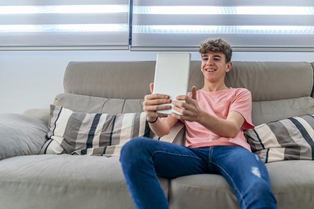Довольно молодой мальчик-подросток делает видеозвонок с помощью планшета. передний план