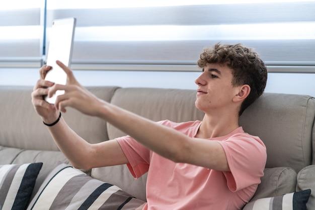 태블릿으로 화상 통화를 하는 꽤 어린 십대 소년