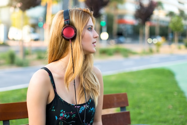 Pretty young teenager girl in a park listening to music with headphones