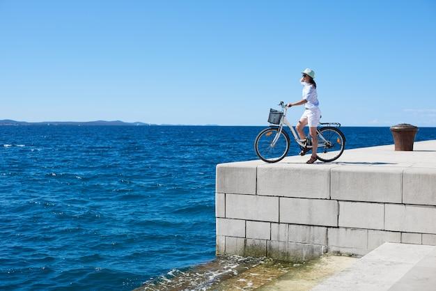 Велосипед довольно молодой туристской женщины задействуя на высоком вымощенном каменном тротуаре на ясных голубых морской воде и небе. красивый летний пейзаж в яркий солнечный день.