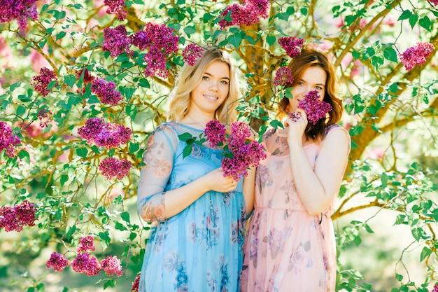 日当たりの良い公園でポーズをとってかなり若い双子の姉妹。