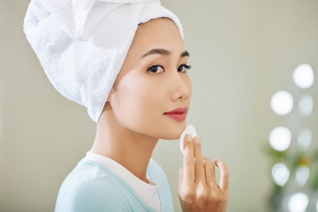 Pretty young vietnamese woman applying toner on her skin after washing face