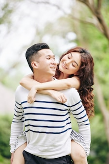 Pretty young vietnamese woman in love looking at boyfriend and hugging him from behid when they are standing in park