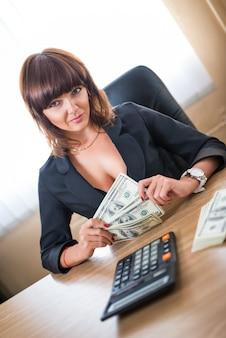 예쁜 젊은 여성 회계사는 책상 위에 달러와 계산기를 들고 사무실 테이블에 앉아 수입을 계산합니다. 급여와 성공 개념
