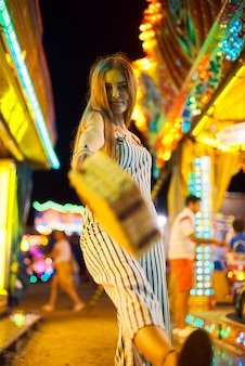 Pretty young woman against the background of magical bright carousel lights.