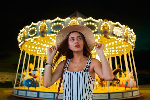 魔法の明るいカルーセルライトを背景にかなり若い女性。