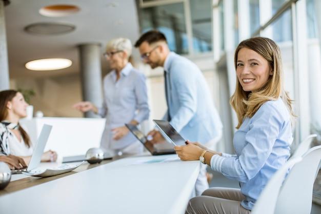 Довольно молодая женщина и группа деловых людей встречаются и работают в офисе