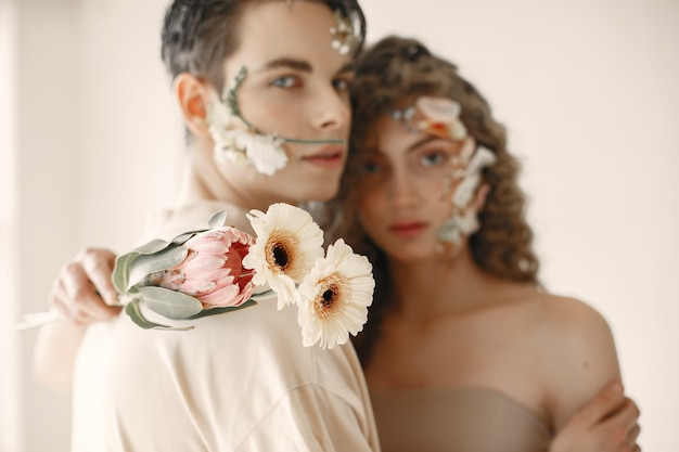 Симпатичная молодая женщина и красивый мужчина с цветами устроили фотосессию