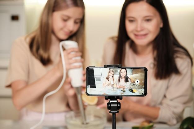 Довольно молодая женщина и ее дочь-подросток готовят мороженое на экране смартфона во время прямой трансляции обучения домашней кулинарии