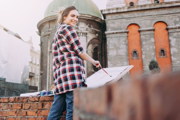 Pretty young woman artist paints old architecture in the city.