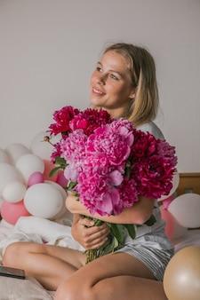 Красивая молодая женщина дома в спальне в постели с цветами в руках делает селфи по мобильному телефону