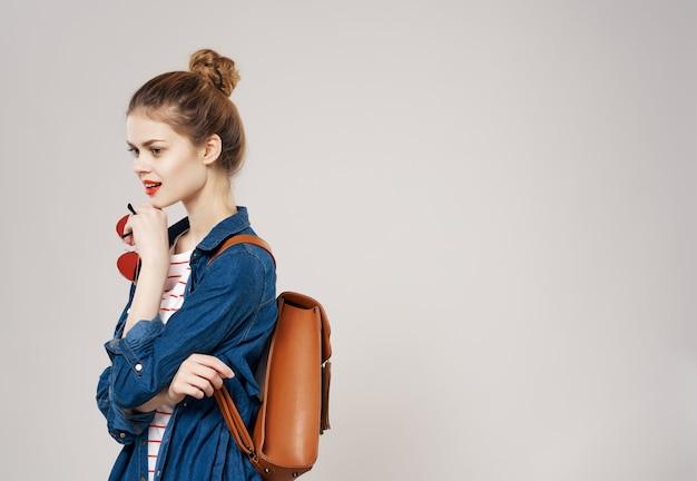 かなり若い女性のバックパック学校の学生のモダンなスタイル