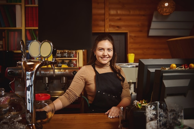 Pretty young woman barista in apron behind the bar in a wooden cafeteria, smiling while looking at camera