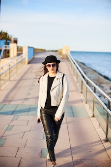 Pretty young woman in black hat walking by the sea