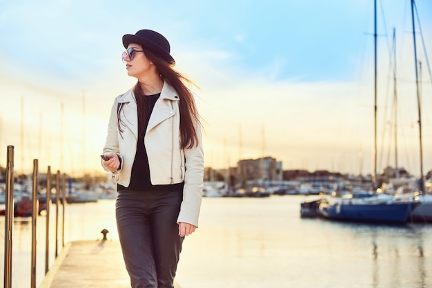 Pretty young woman in black hat with vape at a sea port