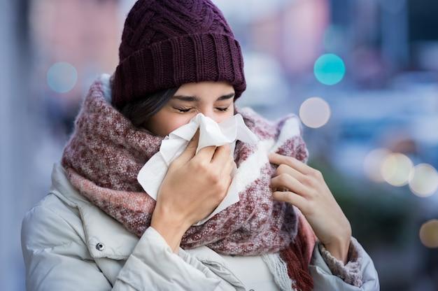 冬に屋外のティッシュで彼女の鼻を吹くかなり若い女性