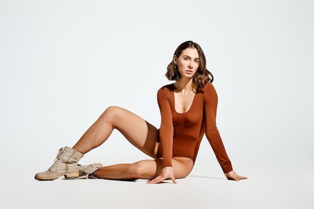 Pretty young woman in brown bodysuit and suede boots sits on the floor in studio