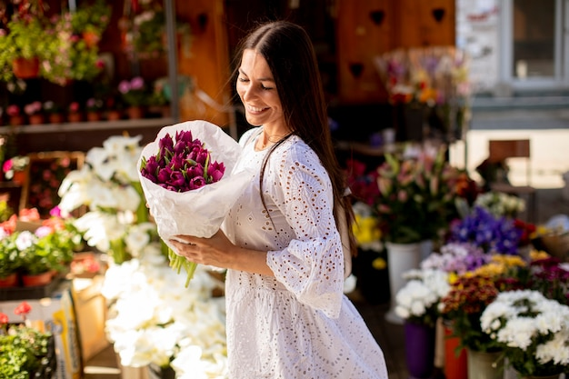 Pretty young woman buying flowers at the flower market