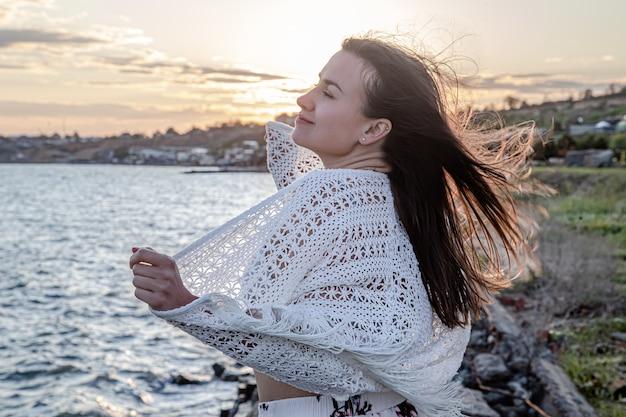 해질녘 바다로 예쁜 젊은 여자. 아름다운 자연.