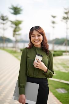Довольно молодая женщина несет чашку кофе на вынос и папку в городском парке, ослепительно улыбаясь в камеру