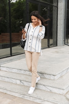 Pretty young woman in casual clothes talking on cellphone with earpods while standing over building