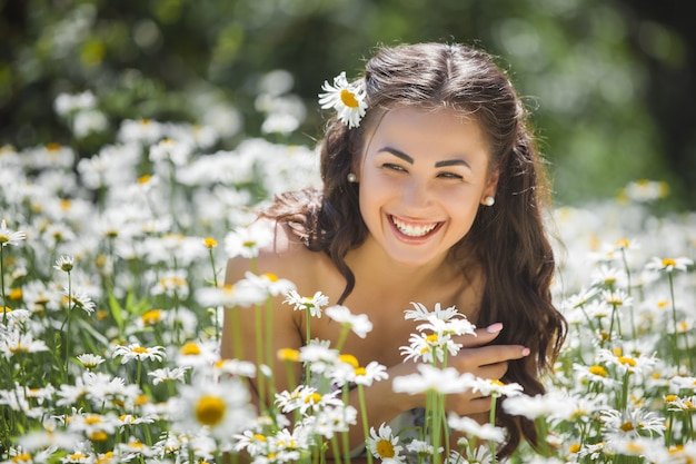 Pretty young woman in the chamomile field. beautiful girl with flowers