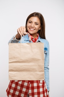 Pretty young woman in check dress holding paper shopping bag