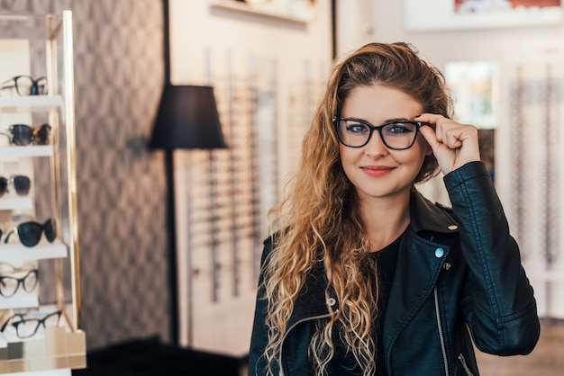 Pretty, young woman choosing new glasses frames in an optician store.