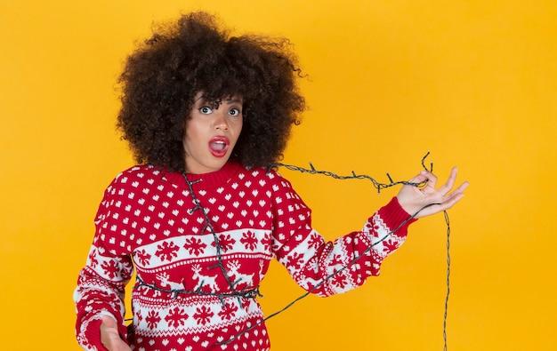Pretty young woman at christmas tangled with christmas lights